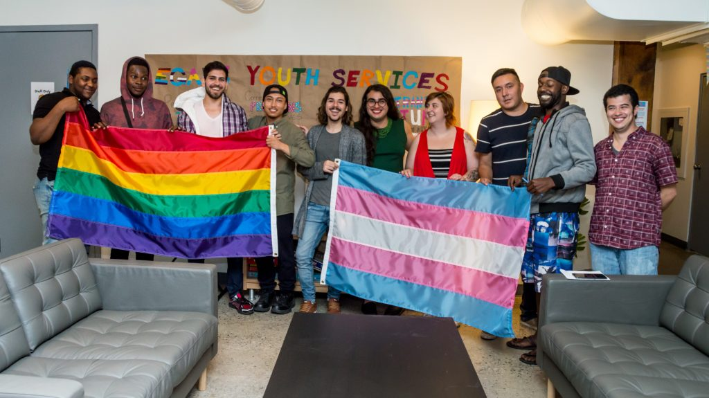 group of youth holding pride flags