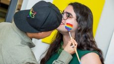 person getting a pride flag face painted on their cheek