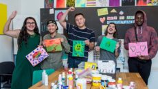 group holding their artwork